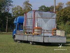 Vzduchotechnická jednotka připravená na korbě nákladního auta k vzdušnému transportu. Protože se bude zasouvat otvorem do budovy jsou na rozích matrace k ztlumení případného kontaktu se stěnou.